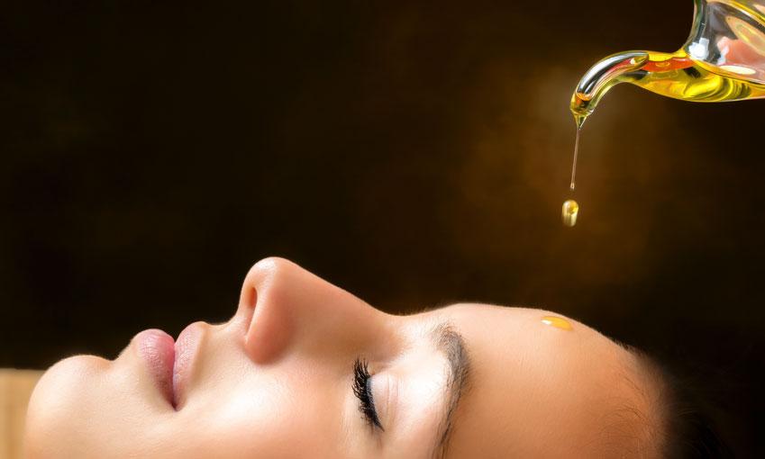 ein Öltropfen trifft genau in die Mitte der Stirn einer liegenden Frau