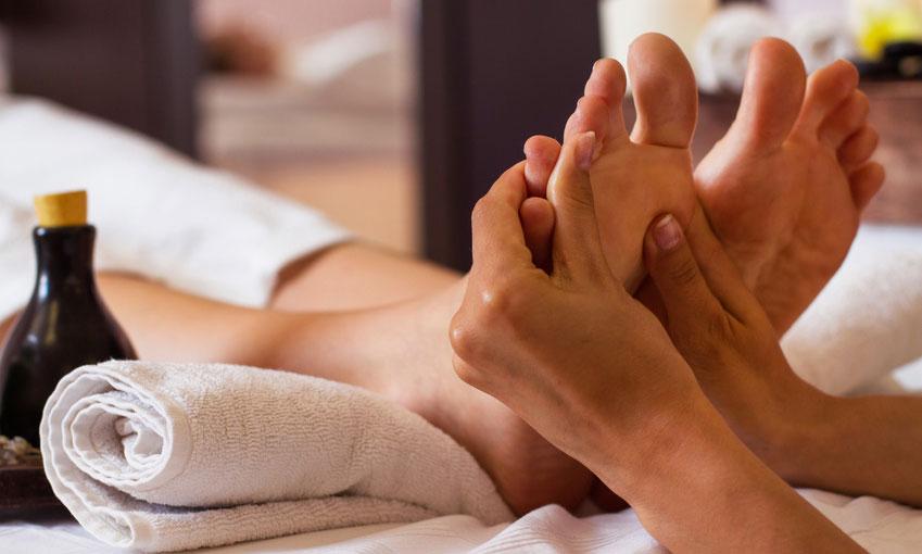 Hände, die eine Fußmassage durchführen