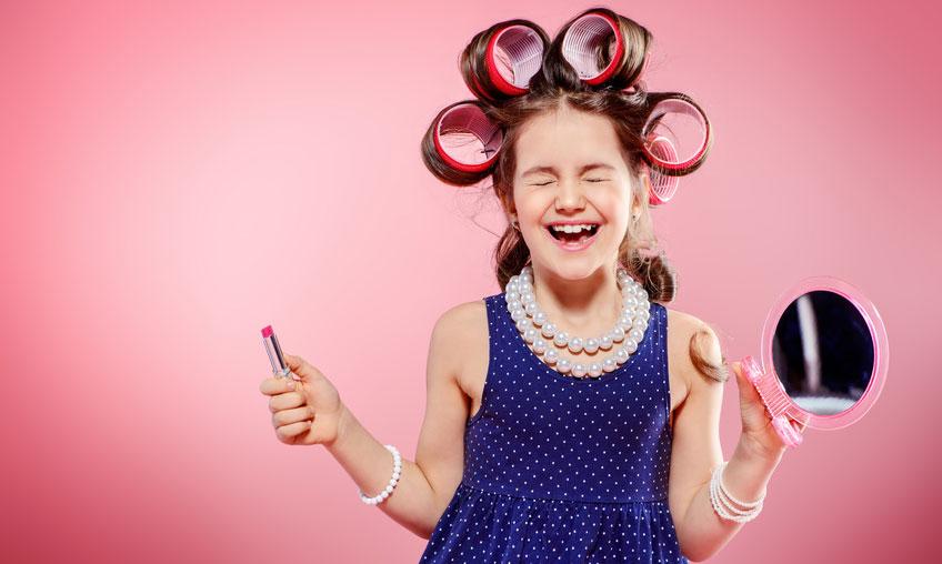 Mädchen mit Riesen-Lockenwicklern, großer Perlenkette, Kosmetikspiegel und pinken Lippenstift