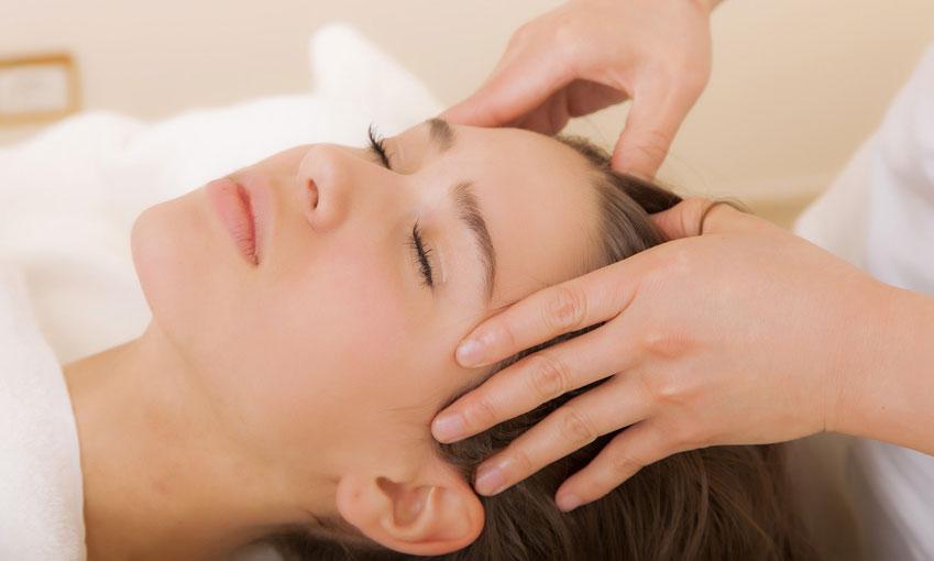 Hände die eine Kopfmassage durchführen