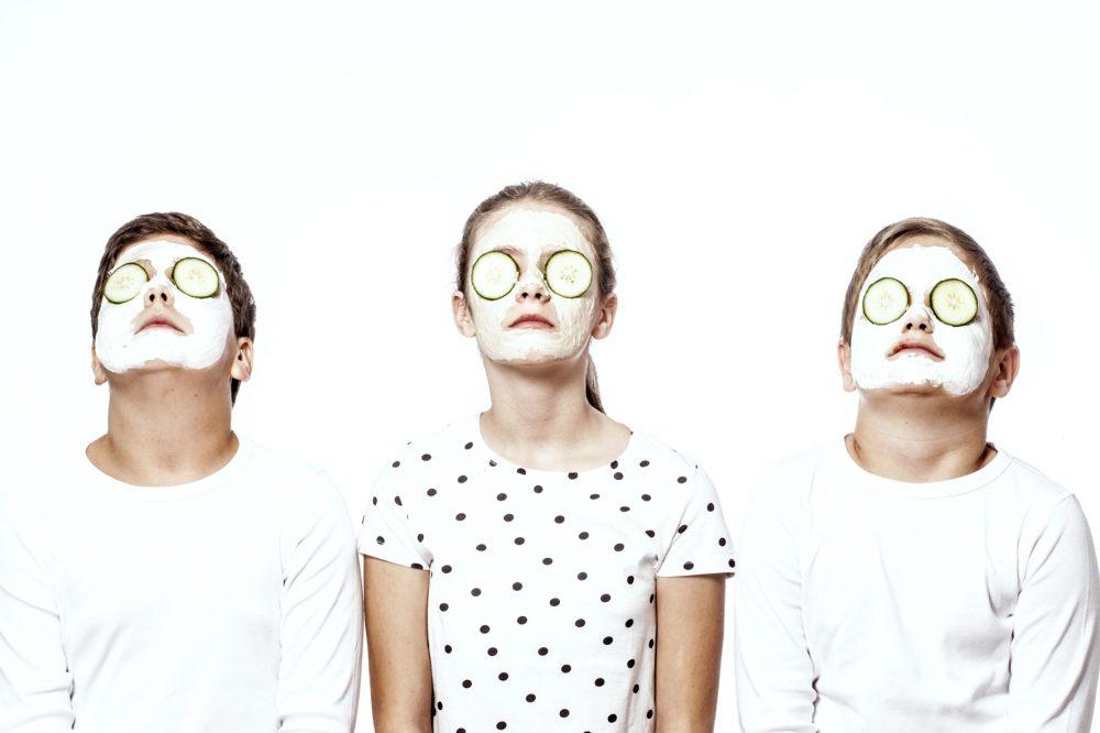3 Kinder mit Gesichtsmaske und Gurken-Augen-Pads
